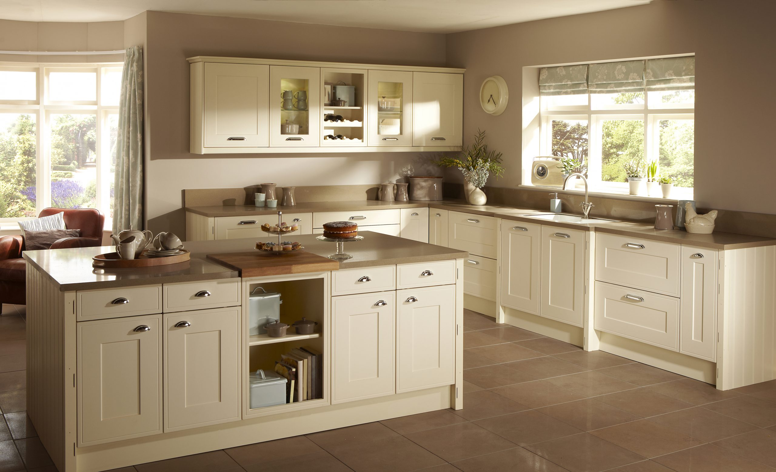 Image of a traditional large kitchen Shaker style interior with kitchen accessories with sun shining through the windows